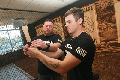 Candace H. Johnson-for Shaw Media Jason Wright, of Libertyville, owner, shows his son, Tristan, 20, how to hold a hatchet before throwing it at a target during the grand opening of the Lumberjaxe Axe Lounge on Peterson Road in Libertyville.  (10/1/21)