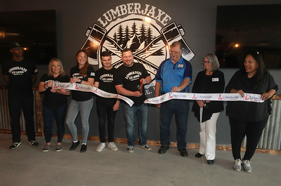 Candace H. Johnson-for Shaw Media Jason Wright, of Libertyville, owner, (center) cuts the ribbon next to his son, Tristan, 20, (on his left) with staff and dignitaries on hand for the ribbon cutting ceremony during the grand opening of the Lumberjaxe Axe Lounge on Peterson Road in Libertyville.  (10/1/21)