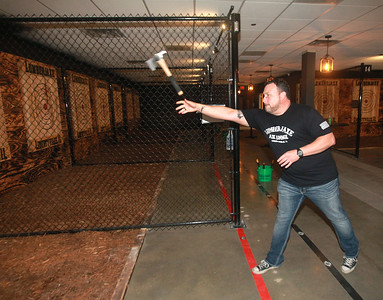 Candace H. Johnson-for Shaw Media Jason Wright, of Libertyville, owner, stands in the pit area as he throws a hatchet at the target during the grand opening of the Lumberjaxe Axe Lounge on Peterson Road in Libertyville.  (10/1/21)