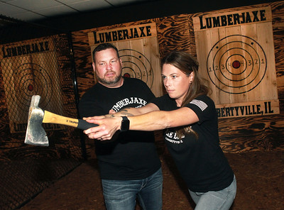 Candace H. Johnson-for Shaw Media Jason Wright, of Libertyville, owner, works with Molly Trefry, of Ingleside, manager, on teaching her how to throw a hatchet at a target during the grand opening of the Lumberjaxe Axe Lounge on Peterson Road in Libertyville. A second location for the Lumberjaxe Axe Lounge will open in Gurnee Mills at the end of November.  (10/1/21)