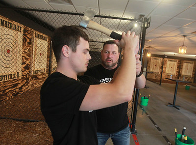 Candace H. Johnson-for Shaw Media Tristan Wright, 20, of Libertyville gets some tips on hatchet throwing to a target from his father, Jason, owner, during the grand opening of the Lumberjaxe Axe Lounge on Peterson Road in Libertyville. A second location for the Lumberjaxe Axe Lounge will open in Gurnee Mills at the end of November.  (10/1/21)