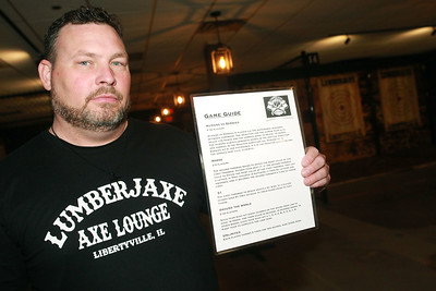 Candace H. Johnson-for Shaw Media Jason Wright, of Libertyville, owner, holds up a game guide showing the different games people can play throwing a hatchet at a target during the grand opening of the Lumberjaxe Axe Lounge on Peterson Road in Libertyville.  (10/1/21)