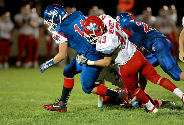Marian Central's Steven Wember (43) takes down Marmion Academy quarterback Brock Krueger during their game at Marmion Academy in Aurora Friday night.