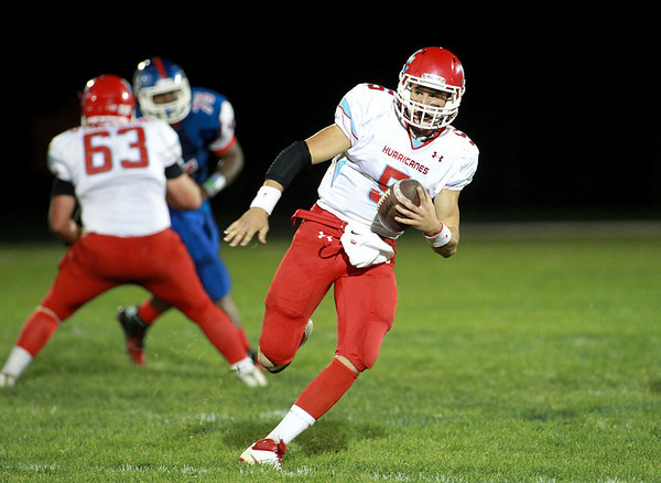 Marian Central quarterback Chris Streveler keeps the ball during their game at Marmion Academy in Aurora Friday night.
