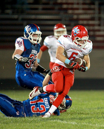 Troy Milone of Marian Central (6) gets past Marmion's Tom Jude (13) during their game in Aurora Friday night.