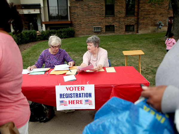 Jean Pierce (right) and Barbara King of the League of Women Voters registers residents of Batavia Apartments to vote during a voter registration drive at the complex.
