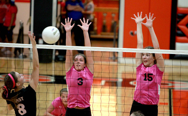 St. Charles North's Emily Belz (3) and Alex Stone (15) try to block a shot from St. Charles East's Emma Johnson during East's 25-21, 25-12 win Tuesday night.