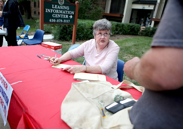 Jean Pierce of the League of Women Voters registers a resident of Batavia Apartments to vote during a voter registration drive at the complex.