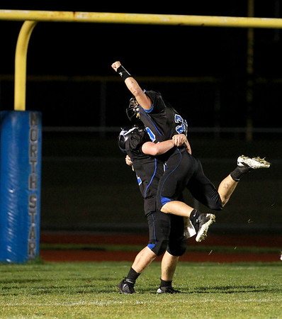 St. Charles North players celebrate a touchdown in the first half of their game against Geneva Friday night.