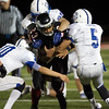 Karen Naess For The Kane County Chronicle<br />   Aurora Christian's Joel Bouagnon runs with the ball as  St. Francis defense tries to stop him on Friday in Aurora.