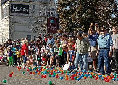 Brett Moist/ for the Northwest Herald.  Onlookers watch their numbered ball in hopes of winning the Great Ball Race during the annual Johnny Appleseed Festival in Downtown Crystal Lake on Saturday.