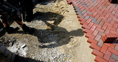 H. Rick Bamman -hbamman@shawmedia.com Former Algonquin firefighter Dan Killian of Algonquin casts his shadow during work Wednesday at the site of the firefighter memorial at Algonquin's Riverfront Park. The memorial will pay homage to those who died during the Sept. 11, 2001, attacks and two firefighters who died in the line of duty for the Algonquin-Lake in the Hills Fire Protection District. Money for the $30,000 memorial came from fundraisers held by the firefighters association.
