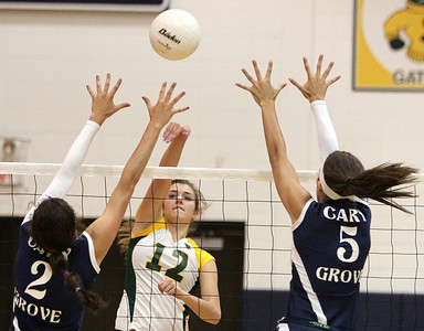 Mike Greene - mgreene@shawmedia.com Crystal Lake South's Nicole Slimko (center) hits the ball over the net as Cary-Grove's Alex Larsen (left) and Kayli Trausch attempt to defend during a match  Thursday, September 27, 2012 at Cary-Grove High School in Cary. Crystal Lake South (19-6) defeated Cary-Grove (10-9) in straight sets.