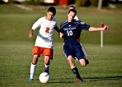 Josh Peckler - Jpeckler@shawmedia.com Cary-Grove's Dale Opasser (10) and Mchenry's Eric Duarte battle for possession of the ball during the first half at Mchenry High School Monday, September 24, 2012.