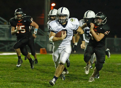 Brett Moist/ For the Northwest Herald  Cary Grove quarter back Quinn Baker runs past Mchenry's Micah Kohn during the 2nd Quarter of Gameplay at Mchenry High School on Friday. Cary Grove defeated Mchenry 42-3. Mchenry's Garrett Glueck (left) was also in pursuit.