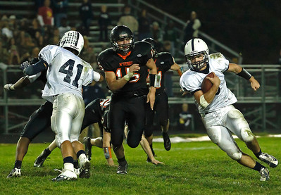 Brett Moist/ For the Northwest Herald  Cary Grove quarter back Quinn Baker runs past Mchenry's Garrett Glueck during the 2nd Quarter of Gameplay at Mchenry High School on Friday. Cary Grove defeated Mchenry 42-3.