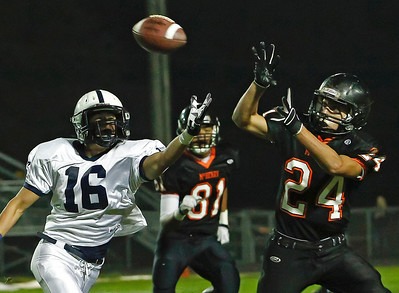 Brett Moist/ For the Northwest Herald  Mchenry's Korey Partenheimer (right) intercept's a pass intended for Cary Grove's Kaene Connington (left) during the 1st Quarter of Gameplay at Mchenry High School on Friday. Mchenry's Dennis Quitilag (back) was in pursuit.  Cary Grove defeated Mchenry 42-3.