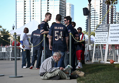 Josh Peckler - Jpeckler@shawmedia.com  A man reads a newspaper while waiting in line to enter Soldier Field before the Bears took on the Indianapolis Colts Sunday, September 9, 2012. The Bears defeated the Colts 41- 21 in the season opener in Chicago.