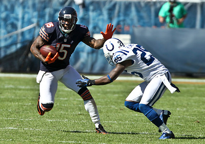 Josh Peckler - Jpeckler@shawmedia.com The Chicago Bears' Brandon Marshall (15) attempts to stiff arms the Indianapolis Colt's Jerraud Powers after receiving a pass in the forth quarter at Soldier Field Sunday, September 9, 2012. The Bears defeated the Colts 41- 21 in the season opener in Chicago.