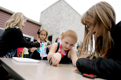 Sarah Nader - snader@shawmedia.com Sydney Hedderich (left), 6, of Carpentersville, Hayley D'Alexander, 6, of Carpentersville, Ella Van Gheem, 6, of Gilberts and Morgan Tamraz, 7, of Gilberts make yellow ribbons to where while attending a rally for childhood cancer awareness month at Cambridge Lakes Charter School in Pingree Grove on Thursday, September 27, 2012. Van Gheem was diagnoses with Leukemia two years ago and is still receiving treatment.