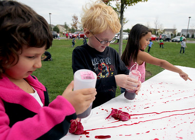 Sarah Nader - snader@shawmedia.com Sophia Lemus (left), 6, of Carpentersville , Ben Waever, 6, of Algonquin and Kiley Quezada, 7, of Gilberts make tie dye bandanas  while attending a rally for childhood cancer awareness month at Cambridge Lakes Charter School in Pingree Grove on Thursday, September 27, 2012.