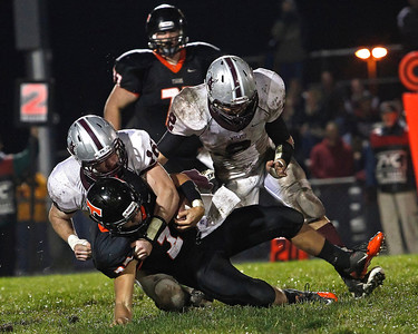 Brett Moist / For the Northwest Herald Crystal Lake Central's Kevin Peisker runs for a gain during the 1st quarter of gameplay against Prairie Ridge at Crystal Lake Central High School on Friday, September 21, 2012. Prairie Ridge's Sean Folliard (left) made the tackle and Nathan Kirchberg (right) was in pursuit. Crystal Lake Central defeated Prairie Ridge 7-3.