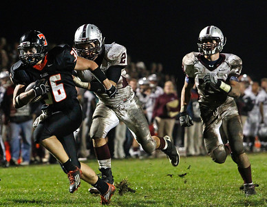 Brett Moist / For the Northwest Herald Crystal Lake Central's Tyler Jenkins runs past Prairie RIdge's Nathan Kirchberg (left) and Austin Nirva (right) at Crystal Lake Central High School on Friday, September 21, 2012. Crystal Lake Central defeated Prairie Ridge 7-3.