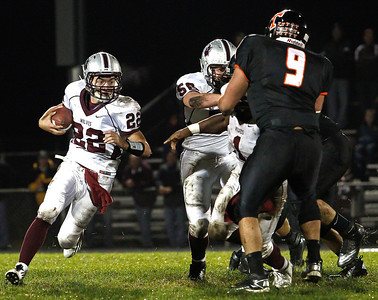 Brett Moist / For the Northwest Herald Prairie Ridge Quarterback Brent Anderson runs past Crystal Lake Central's Kyle Logan during the 1st quarter of gameplay against Prairie Ridge at Crystal Lake Central High School on Friday, September 21, 2012. Crystal Lake Central defeated Prairie Ridge 7-3.