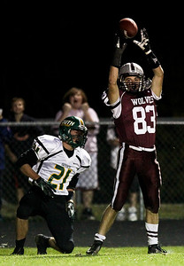 Josh Peckler - Jpeckler@shawmedia.com Prairie Ridge's Ross Carpenter holds up the football after making a catch in front of Crystal Lake South's Brandon LaPak (21) during the first quarter at Prairie Ridge High School Friday, September 28, 2012.