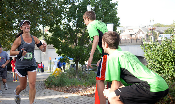 Geneva High School X-Country athletes hand out water to the Fox Valley Marathon runners in Geneva Sunday morning.