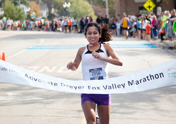 The female winner of the Fox Valley Marathon Vanessa Meneses, from Peoria, finishes the race in St. Charles Sunday morning.