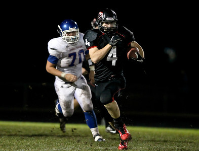 Josh Peckler - Jpeckler@shawmedia.com Huntley's Ethan Connor runs with the ball while being chased by Dundee Crown's Ray Griggle (70) during the first quarter at Huntley High School Friday, September 21, 2012.