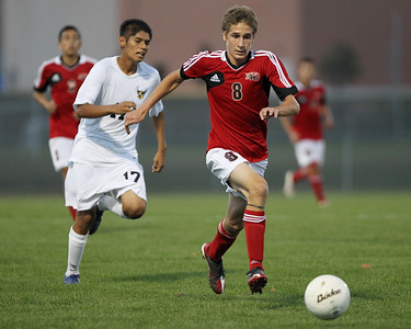 Mike Greene - mgreene@shawmedia.com Huntley's Matt Kitsis dribbles the ball down field while being pursued by Jacobs' Dennis Jiminez during a match Tuesday, September 25, 2012 at Jacobs High School in Algonquin. Huntley came back from a 2-0 second-half deficit to defeat Jacobs' 3-2.