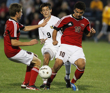 Mike Greene - mgreene@shawmedia.com Huntley's Niko Mihalopoulos (right) hits the ball while Jacobs' Anthony Bux (center) defends during a match Tuesday, September 25, 2012 at Jacobs High School in Algonquin. Huntley came back from a 2-0 second-half deficit to defeat Jacobs' 3-2.