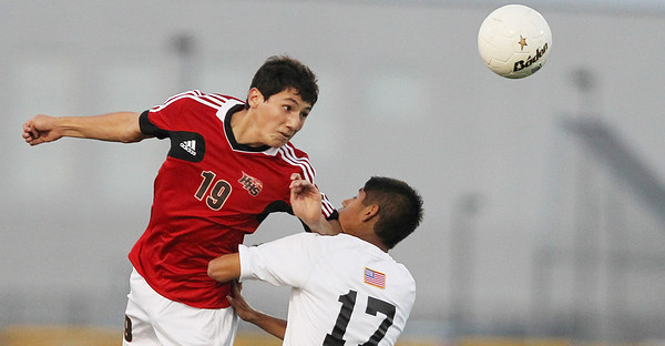 Mike Greene - mgreene@shawmedia.com Huntley's Manuel Menjivar (left) headers a ball as Jacobs' Dennis Jimenez defends during a match against Tuesday, September 25, 2012 at Jacobs High School in Algonquin. Huntley came back from a 2-0 second-half deficit to defeat Jacobs' 3-2.