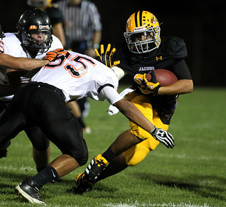 Mike Greene - mgreene@shawmedia.com Jacobs running back Steven Varela puts his arm out to block McHenry cornerback Jake Braskett during a rush in the first quarter of a game Friday, September 14, 2012 at Harry D. Jacobs High School in Algonquin. Jacobs defeated McHenry in a back-and-fourth game 49-42.