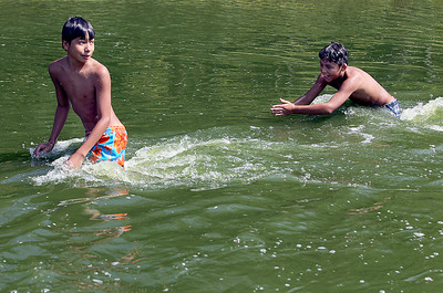 Sarah Nader - snader@shawmedia.com Irbin Bernal (left), 12 and Raul Hernandez, 11, both of Carpentersville try to swim against the Fox River current while enjoying Labor Day at Cornish Park in Algonquin on Monday, September 3, 2012.