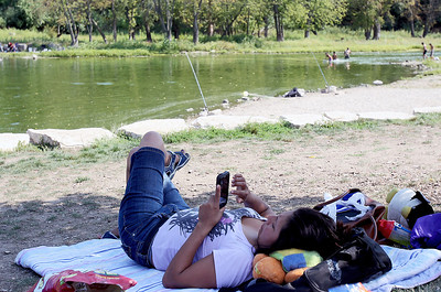 Sarah Nader - snader@shawmedia.com Rubi Vargas of Carpentersville relaxes while enjoying Labor Day on t he side of the Fox River try at Cornish Park in Algonquin on Monday, September 3, 2012.