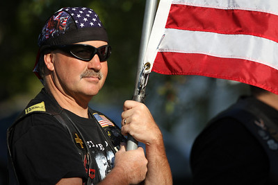Mike Greene - mgreene@shawmedia.com Matt Charlier, of the Warriors' Watch Riders, holds an American flag  during a 9/11 ceremony at Veterans Memorial Park Tuesday, September 11, 2012 in McHenry. The ceremony included the raising of a flag that flew across the street from where Tower 2 of the World Trade Center stood and a moment of silence at 9:05 a.m. marking the time when the South Tower collapsed.