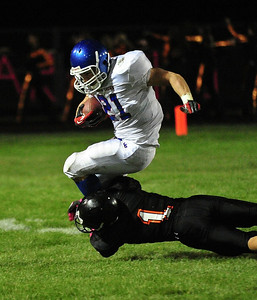 Josh Peckler - Jpeckler@shawmedia.com Dundee-Crown's Cody Lane (21) is tackled by McHenry's Cody Patchett during the first quarter in McHenry Friday, September 7, 2012.