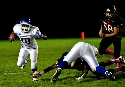 Josh Peckler - Jpeckler@shawmedia.com Dunee-Crown's JT Hill-Beasley (10) runs around blockers while being followed by McHenry's Micah Kohn (58) during the second quarter in McHenry Friday, September 7, 2012.