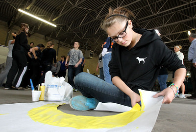 "Mike Greene - mgreene@shawmedia.com McHenry East High School junior Hope Schneider, 16, cuts out a drawing of a moon during a float building event for McHenry High School's Homecoming Monday, October 1, 2012 at the City Garage in McHenry. A parade, with this year's theme of ""Wish Upon a Star,"" will be held Friday, October 5 at 2PM before McHenry faces Johnsburg in a home football contest."