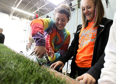 "Mike Greene - mgreene@shawmedia.com McHenry East High School sophomores Katelynn McManus (left), 15, and Caitlyn Busse, 15, laugh while stapling chicken wire to the side of a float during a float building event for McHenry High School's Homecoming Monday, October 1, 2012 at the City Garage in McHenry. A parade, with this year's theme of ""Wish Upon a Star,"" will be held Friday, October 5 at 2PM before McHenry faces Johnsburg in a home football contest."