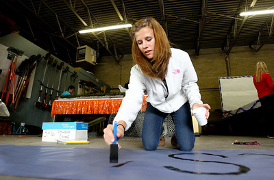 """Mike Greene - mgreene@shawmedia.com McHenry East High School sophomore Sydney Jozwiak, 15, writes a slogan on a sign during a float building event for McHenry High School's Homecoming Monday, October 1, 2012 at the City Garage in McHenry. A parade, with this year's theme of """"Wish Upon a Star,"""" will be held Friday, October 5 at 2PM before McHenry faces Johnsburg in a home football contest."""