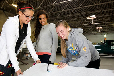 "Mike Greene - mgreene@shawmedia.com McHenry East High School junior Jacqueline Arevalo (left), 16, helps West seniors Josie Hobbs (center), 17, and Laura D'Angelo, 17, cut out styrofoam stars during a float building event for McHenry High School's Homecoming Monday, October 1, 2012 at the City Garage in McHenry. A parade, with this year's theme of ""Wish Upon a Star,"" will be held Friday, October 5 at 2PM before McHenry faces Johnsburg in a home football contest."