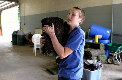 "Mike Greene - mgreene@shawmedia.com McHenry West High School freshman J.P. Dudley, 15, hauls a load of grass to a float during a float building event for McHenry High School's Homecoming Monday, October 1, 2012 at the City Garage in McHenry. A parade, with this year's theme of ""Wish Upon a Star,"" will be held Friday, October 5 at 2PM before McHenry faces Johnsburg in a home football contest."