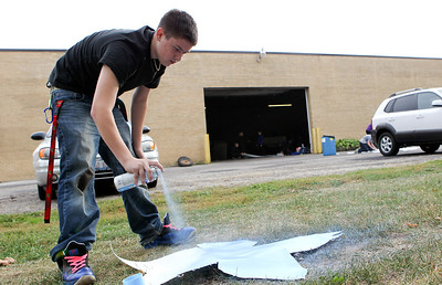 "Mike Greene - mgreene@shawmedia.com McHenry West High School sophomore Jon Arnswald, 15, spray paints a star during a float building event for McHenry High School's Homecoming Monday, October 1, 2012 at the City Garage in McHenry. A parade, with this year's theme of ""Wish Upon a Star,"" will be held Friday, October 5 at 2PM before McHenry faces Johnsburg in a home football contest."