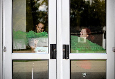 Josh Peckler - Jpeckler@shawmedia.com Alden-Hebron High School juniors Jesi Damato (left) and Jackie LeJevne laugh as they paint green paint onto the windows inside Alden-Hebron High School as they prepare for Homecoming Week.  © Northwest Herald