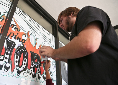 Josh Peckler - Jpeckler@shawmedia.com Jesse Reitz, a senior at Johnsburg High School paints on the outside of a window at Johnsburg High School for Homecoming week. Students in each class were competing against each other to have the best window paintings. © Northwest Herald