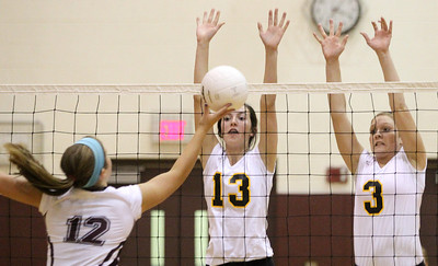 Mike Greene - mgreene@shawmedia.com Jacobs' Katie Mahoney (center) and teammate Alyssa Ehrhardt (right) attempt to block a shot by Prairie Ridge's Mackenzi Humm during the second set of a conference match Tuesday, September 18, 2012 at Prairie Ridge High School in Crystal Lake. Prairie Ridge (4-0) defeated Jacobs (3-1) in three sets to remain undefeated in the conference.